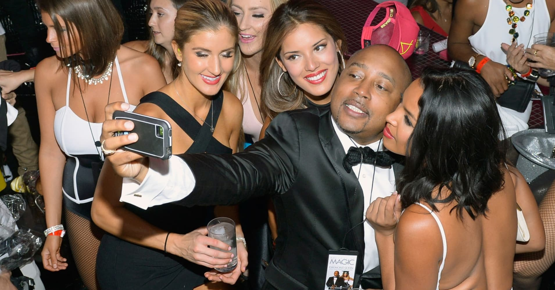 Television personality and Founder, President and CEO of FUBU Daymond John (C) takes a selfie with club goers.