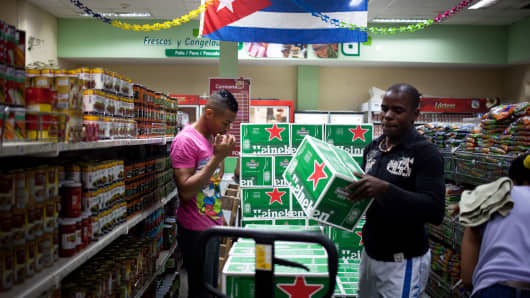 A worker unloads a box of Heineken NV beer from a shipping pallet at a Panamaericana store in Havana, Cuba.