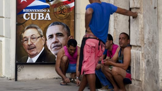 Men sit next to a poster of U.S. President Barack Obama and Cuban President Raul Castro in Old Havana, Cuba.