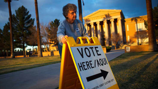A volunteer places a sign to direct voters to a polling station at Kenilworth School in Phoenix, Arizona.