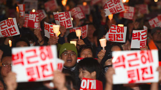 Protesters hold up signs reading 'Step down Park Geun-Hye' during a candle-lit rally in Seoul on October 29, 2016,
