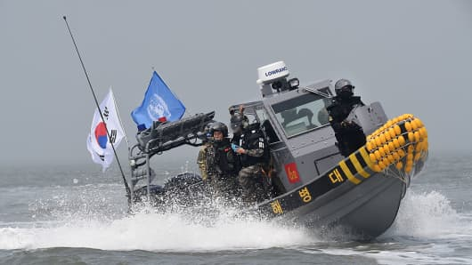South Korean marines and navy soldiers on a boat conduct a crackdown against China's illegal fishing in neutral waters on June 10, 2016.