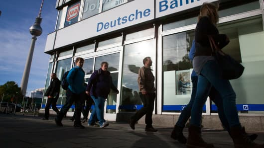 Pedestrians pass a branch of Deutsche Bank in Berlin, Germany.