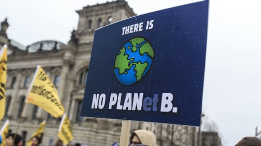 Activists participate in the Global Climate March in front of the Reichstag Building on November 29, 2015