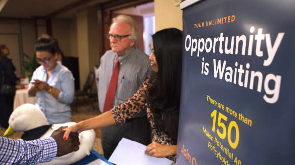 An Aflac representative, right, shakes hands with a job seeker during an Orange County Choice Career Fair in Santa Ana, California.