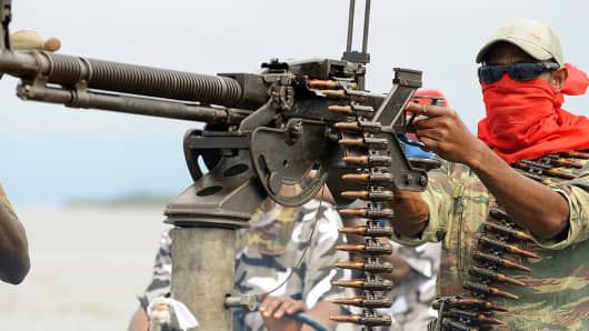 A Niger Delta fighter poses with a heavy machine-gun at his militia's creek camp.