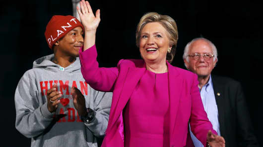 Recording artist Pharrell Williams, left, Hillary Clinton and Sen Bernie Sanders (I-VT), right, greet supporters during a campaign rally November 3, 2016 in Raleigh, North Carolina.