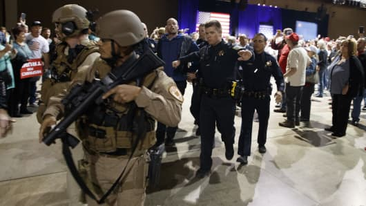 A man is escorted by law enforcement officers moments after Republican presidential candidate Donald Trump was rushed offstage by Secret Service agents during a campaign rally in Reno, Nev., on Saturday, Nov. 5, 2016.