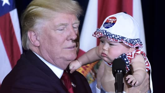 Republican presidential nominee Donald Trump holds a baby during a rally in the Special Events Center of the Florida State Fairgrounds in Tampa, Florida on November 5, 2016.