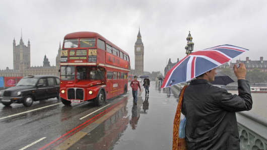 People, one with a Union Jack umbrella, walk across Westminster Bridge towards the Houses of Parliament on a wet, September afternoon in London.