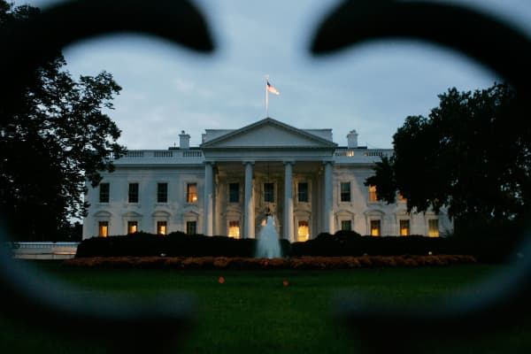 The early morning sun begins to rise behind the White House.
