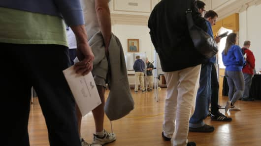 Voters line up to vote as others cast their ballots.