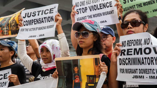A group of protesters from Indonesian migrant worker organisations hold placards and a photo of the victims' family members outside the High Court in Hong Kong.