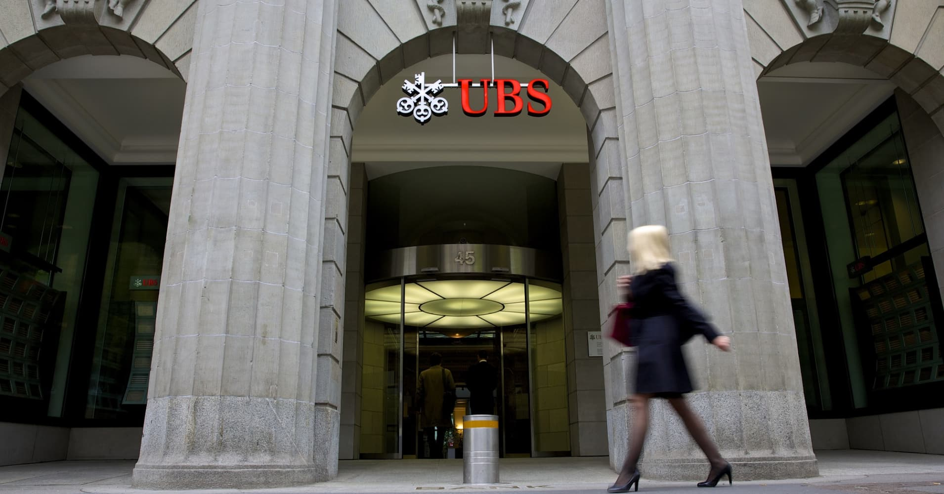 A pedestrian walks past the entrance to UBS AG's headquarters in Zurich, Switzerland.