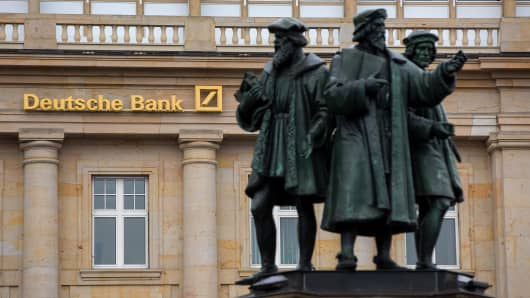 Statues stand outside a Deutsche Bank AG branch in Frankfurt, Germany.