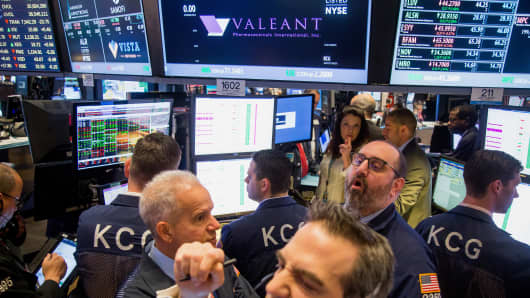 Traders work beneath a monitor displaying Valeant Pharmaceuticals International Inc. signage on the floor of the New York Stock Exchange (NYSE) in New York.
