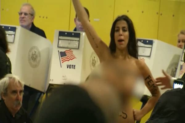 Topless protesters greet voters at Trump polling site and others as election kicks off