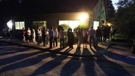 Voters cast shadows as they wait in a line at a polling station in Durham, North Carolina