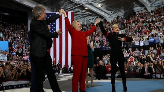 Democratic presidential nominee former Secretary of State Hillary Clinton (C) raises her arms with musicians Jon Bon Jovi (L) and Lady Gaga during a campaign rally at North Carolina State University on November 8, 2016 in Raleigh North Carolina.