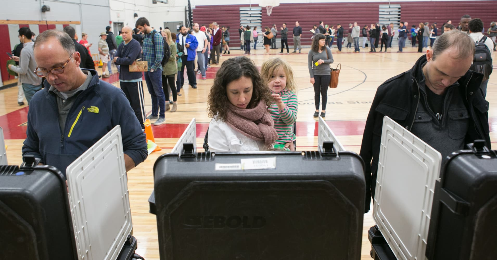After waiting in line for 1.5 hours, Blake Ashe holds her daughter, Julia, 3, as she casts her ballot on election day November 8, 2016 at Grady High School in Atlanta, Georgia.