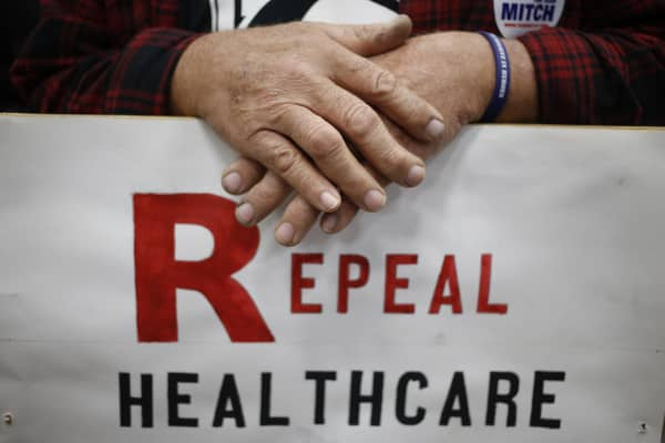 Supporter James Hughes of Louisville, Ky. holds a sign calling for the repeal of the Affordable Care Act during a rally for Senate Minority Leader Mitch McConnell (R-KY) at Brandeis Machinery & Supply Company on October 31, 2014 in Louisville, Kentucky.