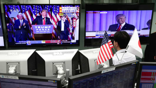 An employee of a foreign exchange trading company looks at monitors displaying TV news of Republican President-elect Donald Trump as he gives his victory speech after U.S. presidential election at a foreign exchange trading company on November 9, 2016 in Tokyo, Japan.