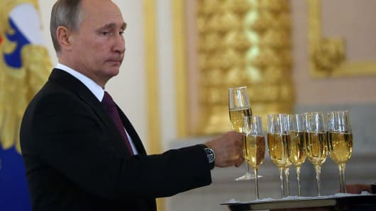 Russian President Vladimir Putin takes a glass of champagne during the reception for new foreign ambassadors at Grand Kremlin Palace in Moscow, Russia, on November 9, 2016.
