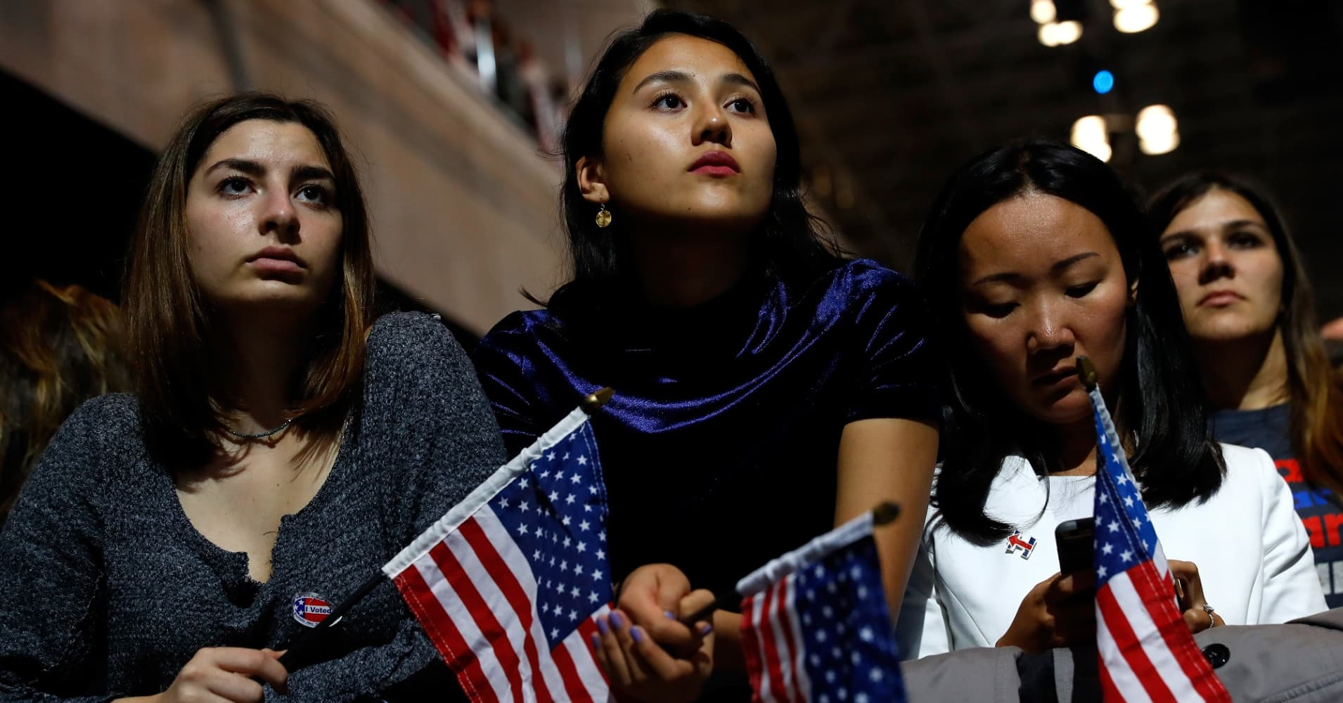 People hold American flags as they watch voting results at the Jacob K. Javits Convention Center on November 8, 2016.