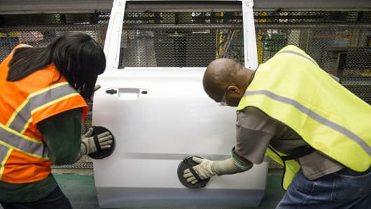 Employees work on a door on the production line at a General Motors assembly plant.