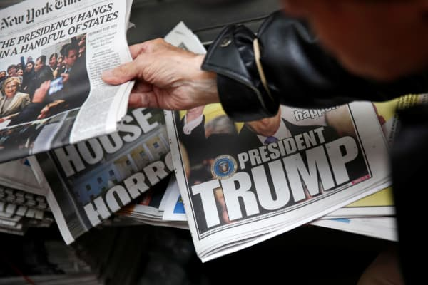 A man hands a newspaper to a customer at a news stand in New York, U.S., November 9, 2016.