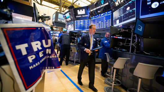 A trader walks past a campaign sign for U.S. President-elect Donald Trump and U.S. Vice President-elect Mike Pence on the floor of the New York Stock Exchange (NYSE) in New York, U.S., on Wednesday, Nov. 9, 2016.