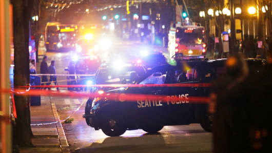 Police cars are staged at the scene of a shooting Wednesday, Nov. 9, 2016, in downtown Seattle.