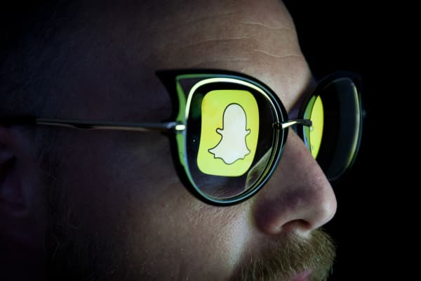 Man wearing glasses with the reflection of Snapchat logo