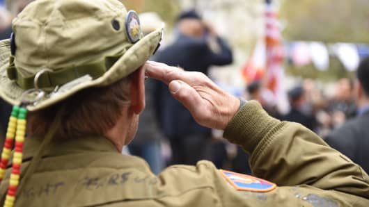 Veteran in well-worn cammos salutes during playing of Star Spangled Banner