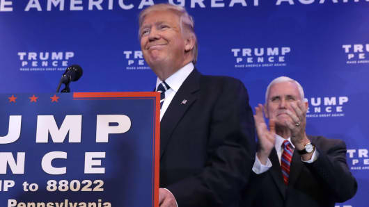 Republican vice presidential nominee Gov. Mike Pence (R) welcomes presidential nominee Donald Trump to the stage during a campaign event about the Affordable Care Act.