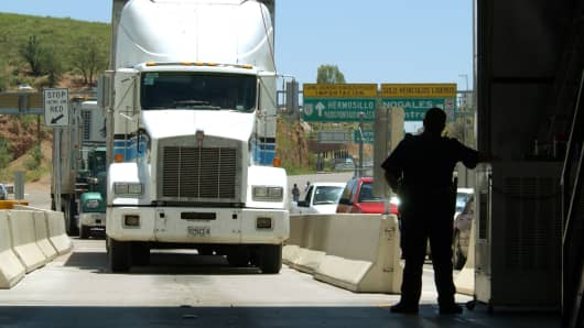 A United States Customs agent waits for a northbound truck crossing the border to enter the United States from Nogales, Sonora, Mexico.