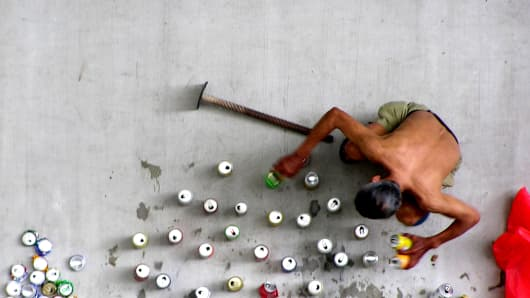 Man crushes empty drink cans, which were collected to be sold off as scrap metal to recycling companies in Singapore.