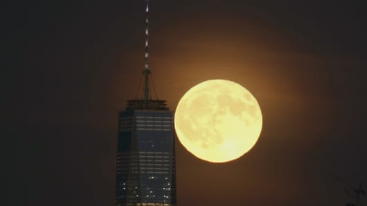 A full harvest moon rises behind Lower Manhattan and One World Trade Center in New York City on September 16, 2016, as seen from Newark, NJ.