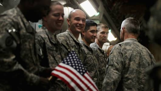Soldiers from the 3rd Brigade, 1st Cavalry Division, celebrate after boarding a C-17 transport plane to depart Camp Adder, now known as Imam Ali Base, on December 17, 2011 near Nasiriyah, Iraq.