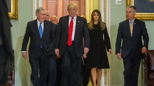Senate Majority Leader Mitch McConnell (R-KY), left, walks with President-elect Donald Trump, center, and Trump's wife Melania, second right, before a meeting at The Capitol Building on November 10.