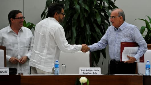 FARC commander Ivan Marquez, center, and the head of the Colombian delegation Humberto de la Calle, right, shake hands after signing the new agreement, with Cuban Foreign Affairs Minister Bruno Rodriguez Parrilla, left, in Havana.