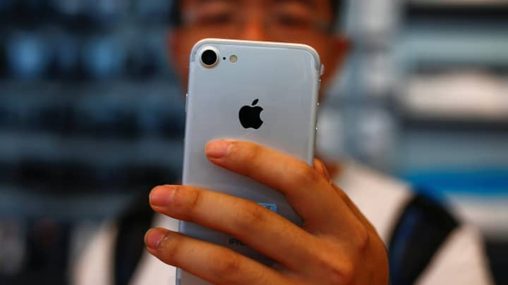 A man holds his new iPhone 7 at an Apple store in Beijing.