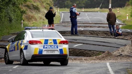 Policemen and locals look at damage following an earthquake, along State Highway One near the town of Ward, south of Blenheim on New Zealand's South Island, November 14, 2016.