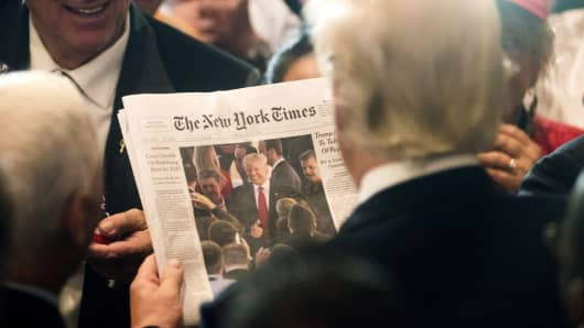 Donald Trump views a photo of himself on the cover of The New York Times during an RNC goodbye reception at the Westin Hotel in Cleveland, on Friday, July 22, 2016.