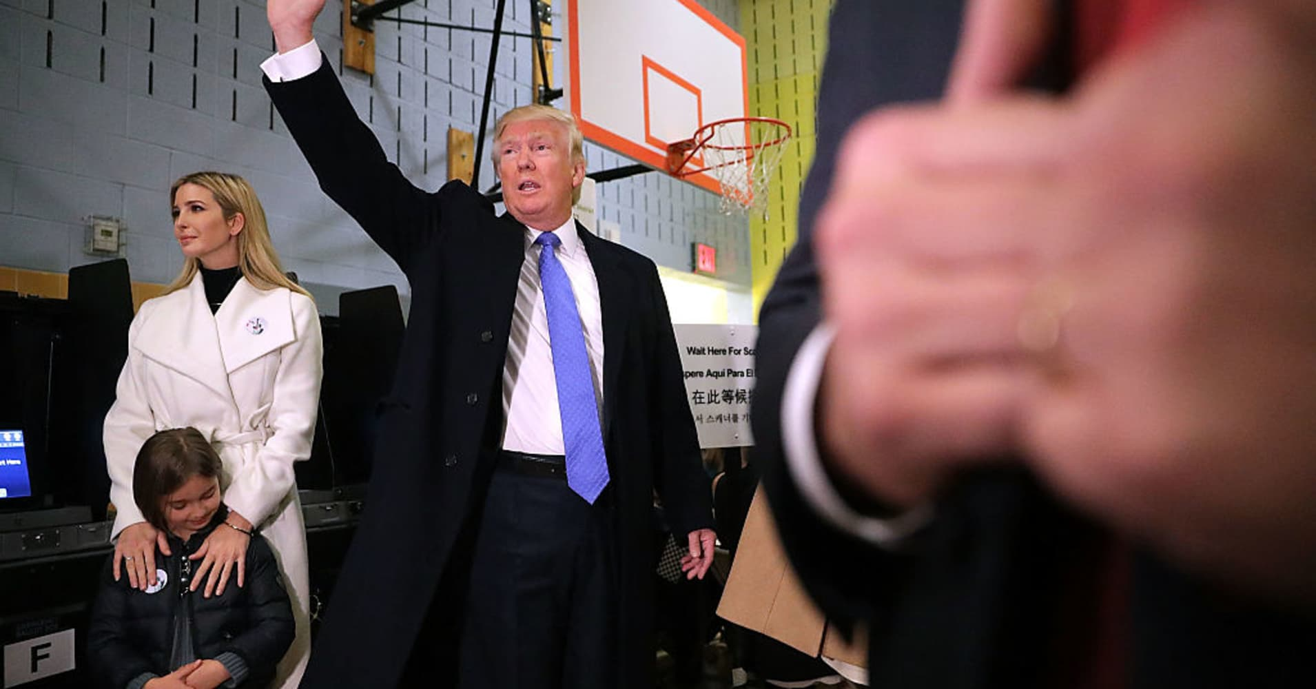 Donald Trump (C) waves after casting his vote with daughter Ivanka Trump (L) and her daughter Arabella Rose Kushner on Election Day at PS 59 November 8, 2016 in New York City.