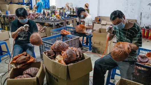 A worker paints a mask of Donald Trump at the Shenzhen Lanbingcai Latex Crafts Factory on October 18, 2016 in Shenzhen, China.