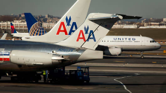 An American Airlines Inc. McDonnell Douglas MD-82 plane sits parked at a gate while a United Continental Holdings plane taxis down the runway at LaGuardia Airport in the Queens borough of New York.