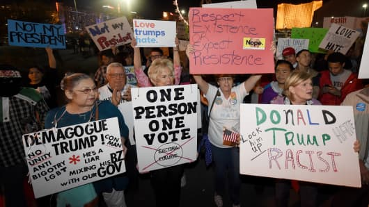 Anti-Donald Trump protesters hold signs as they gather at The Linq Promenade before marching on the Las Vegas Strip on November 12, 2016 in Las Vegas, Nevada.