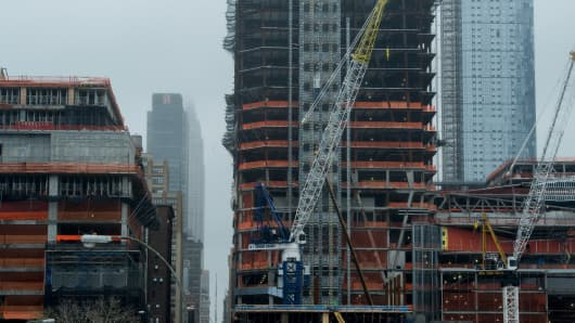 The Empire State Building is seen hidden in the clouds as construction continues at the Hudson Yards project in New York City on October 1, 2016.