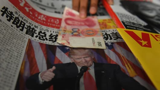 A vendor picks up a 100 yuan note above a newspaper featuring a photo of US president-elect Donald Trump, at a news stand in Beijing on November 10, 2016.